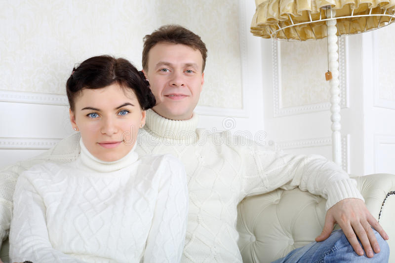 Smiling young husband and wife in white sweaters sit on sofa. Smiling young husband and wife in white sweaters sit on white sofa at home royalty free stock image