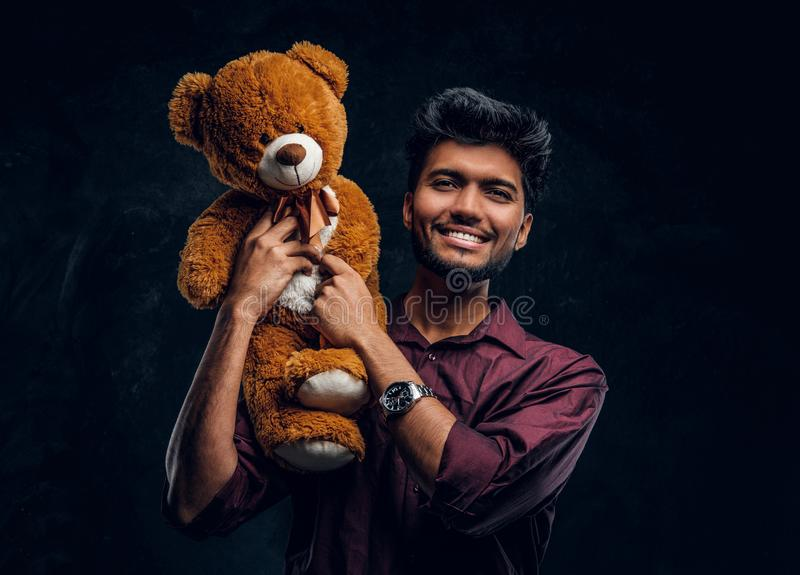 Smiling young Indian man in stylish shirt holding teddy bear and looking at a camera. Studio photo against a dark textured wall royalty free stock images