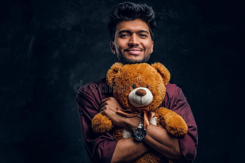 Smiling young Indian man in stylish shirt hugs teddy bear and looking sideways. Studio photo against a dark textured wall stock image