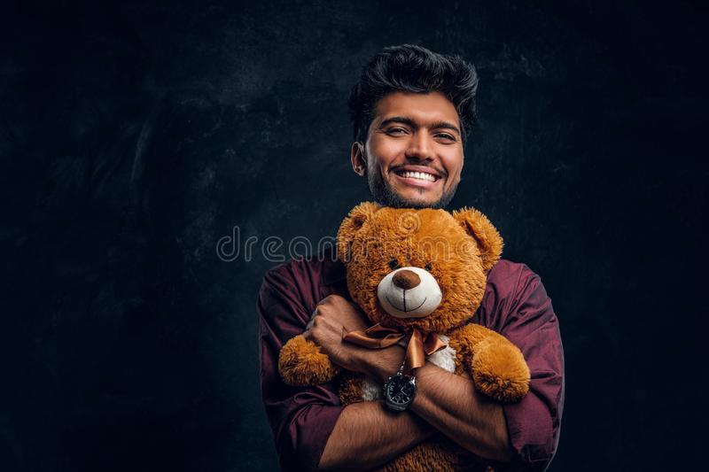 Smiling young Indian man in stylish shirt hugs teddy bear and looking sideways. Studio photo against a dark textured wall royalty free stock photos