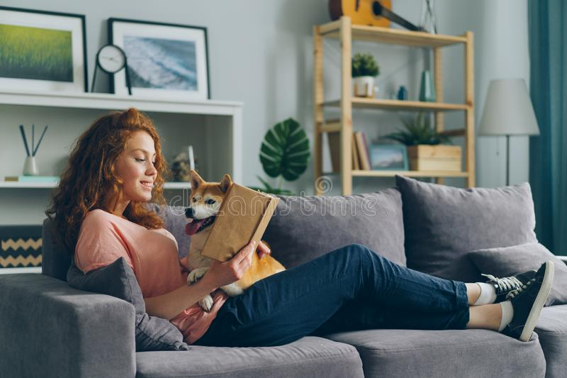 Smiling young lady reading book at home on sofa and hugging cute pet dog royalty free stock photos