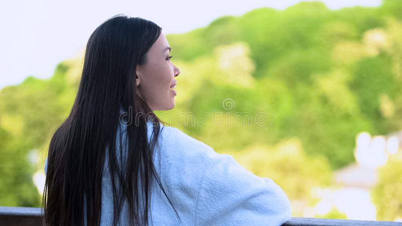 Smiling young lady white bathrobe looking outdoors relaxing spa center balcony royalty free stock photography