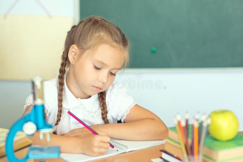 Smiling young little child girl writing in school. Education and school concept.  stock image