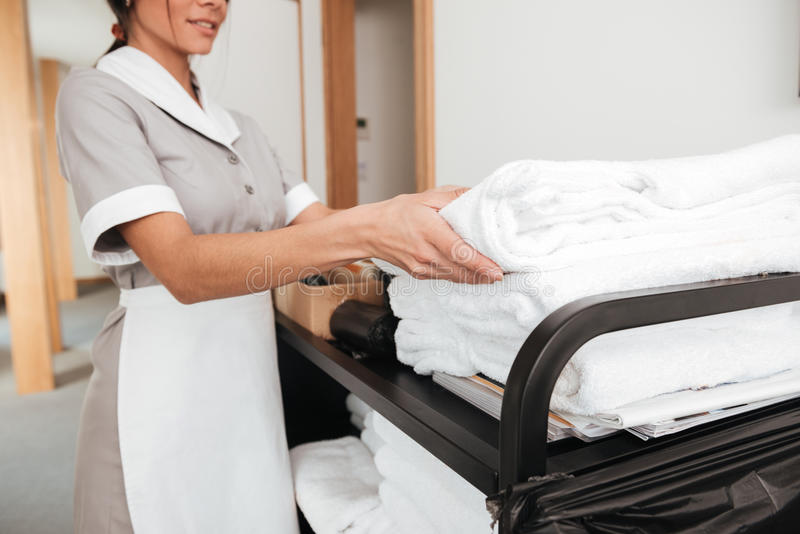 Smiling young maid taking fresh towels from a housekeeping cart stock images
