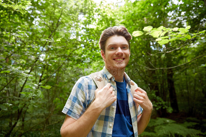 Smiling young man with backpack hiking in woods royalty free stock photography