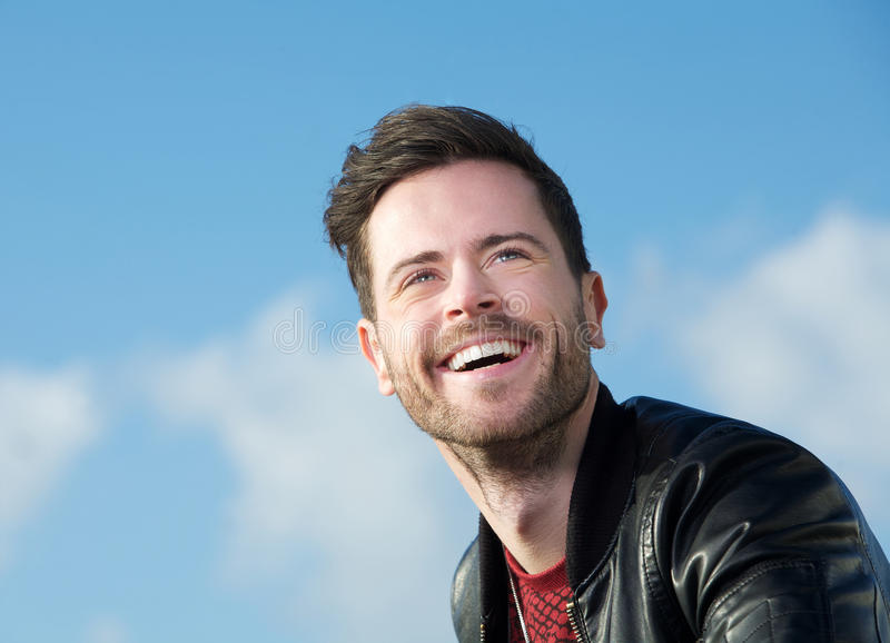 Smiling young man with beard outdoors royalty free stock photography