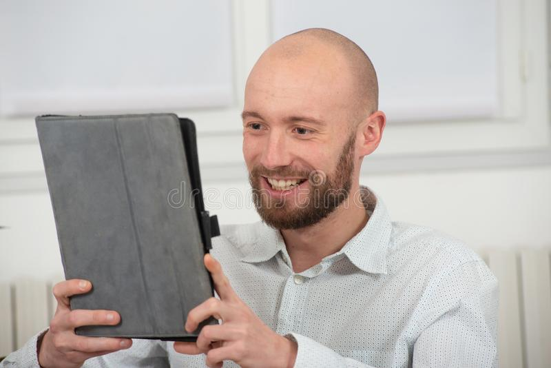 Young man with a beard using a digital tablet. Smiling young man with a beard using a digital tablet royalty free stock photos