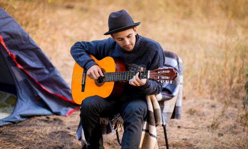Smiling young man in black hat sitting near touristic tent and playing guitar in forest royalty free stock photos
