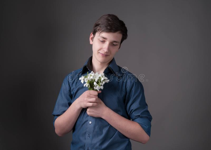 Smiling young man in blue shirt holding and looking at bouquet with white snowdrops. Handsome smiling young man in blue shirt holding and looking at bouquet with royalty free stock photo