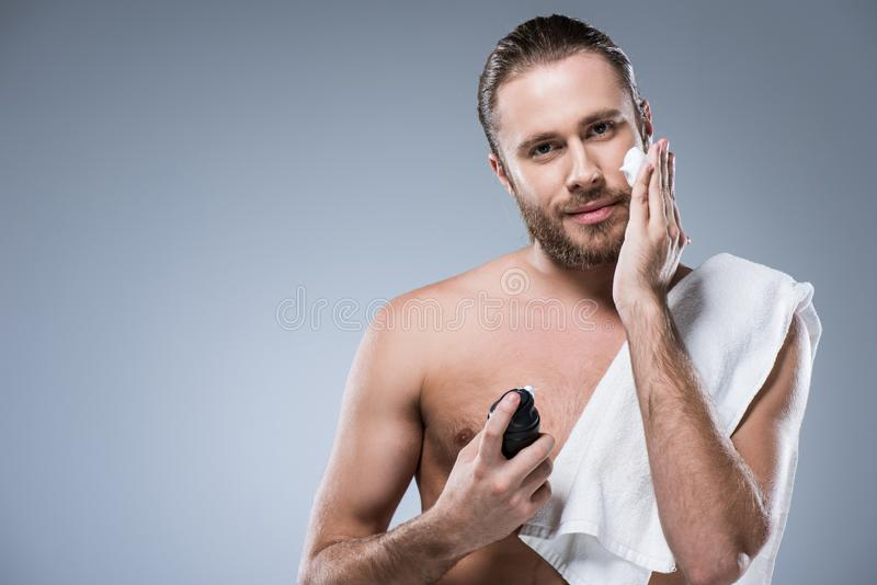 Smiling young man with bottle in hand and towel on shoulder applying shaving foam by another on his cheek, royalty free stock photography