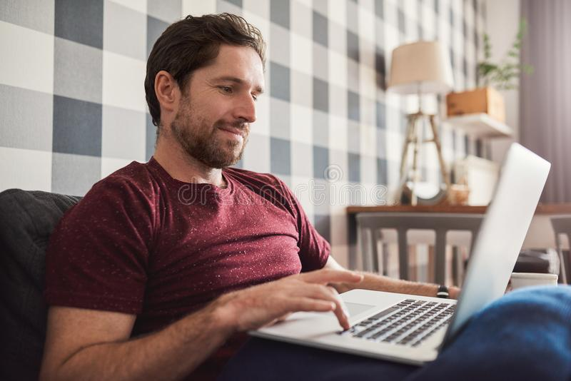 Smiling young man relaxing on his sofa using a laptop stock photos