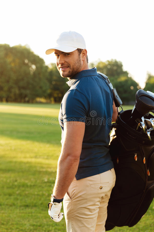 Smiling young man in cap holding golf bag stock photos