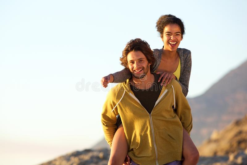 Smiling young man carrying carefree woman on back stock images