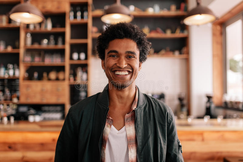 Smiling young man in a coffee shop stock images