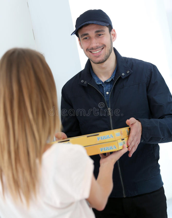 Smiling young man delivering pizzas at home. Smiling young men delivering pizza to customer royalty free stock image