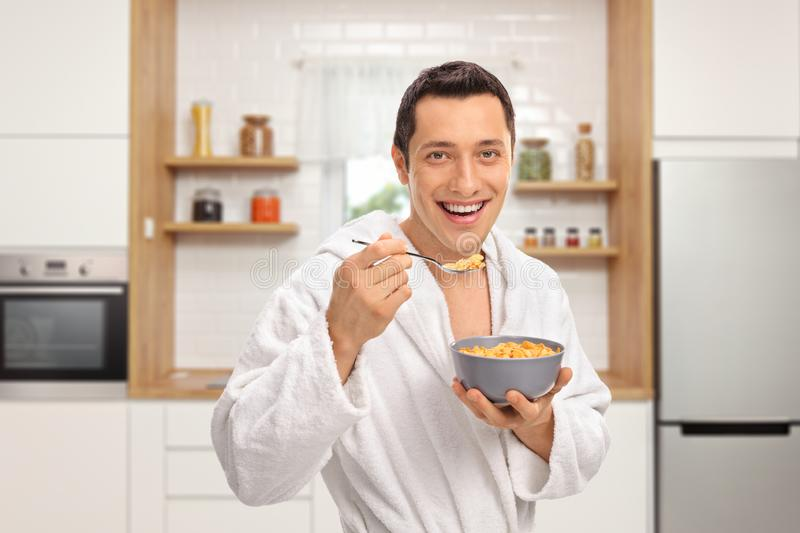 Smiling young man in a dressing gown eating cereal from a bowl in a kitchen stock photo
