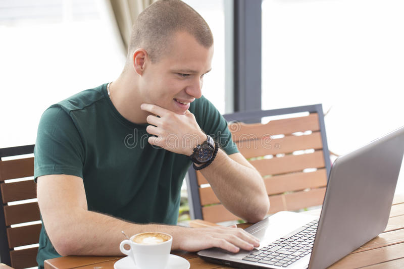 Smiling young man drinking morning coffee and read the important stock photography