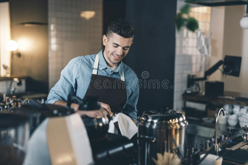 Smiling young man drying clean tamper with soft towel royalty free stock image