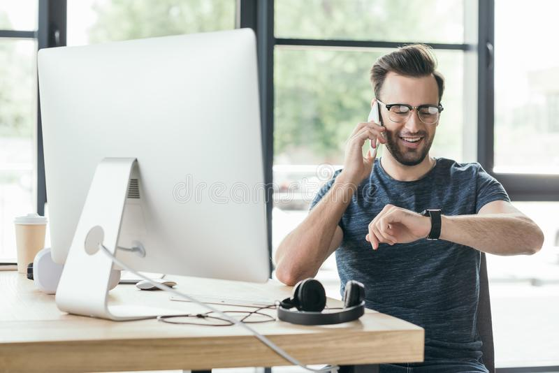 Smiling young man in eyeglasses checking smartwatch and talking by smartphone. At workplace royalty free stock images