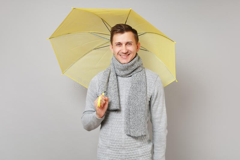 Smiling young man in gray sweater, scarf holding yellow umbrella on grey background studio portrait. Healthy royalty free stock photo