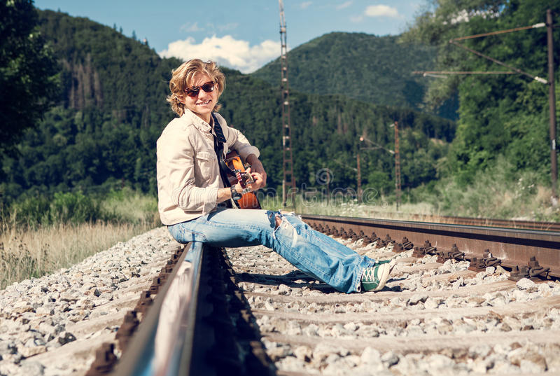 Smiling young man with guitar sitting on the railway royalty free stock photos