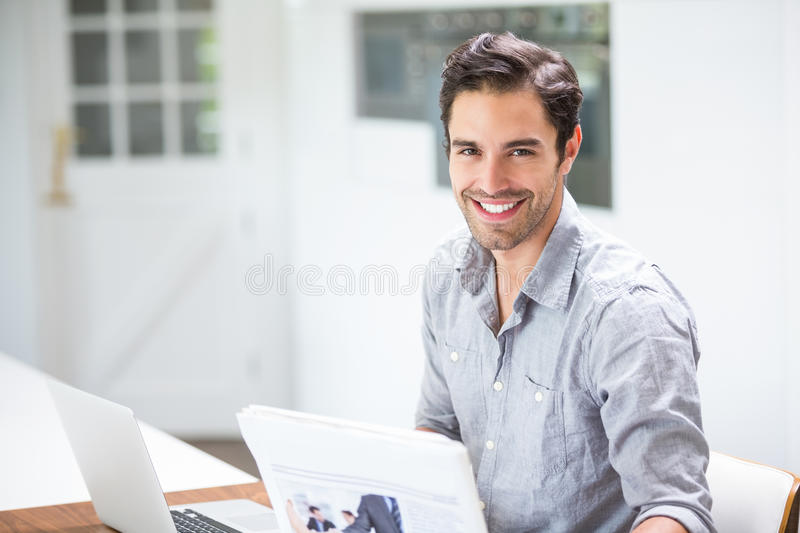 Smiling young man holding documents while sitting at desk with laptop royalty free stock photography