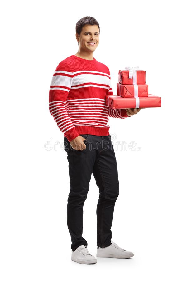 Smiling young man holding gift boxes royalty free stock photography