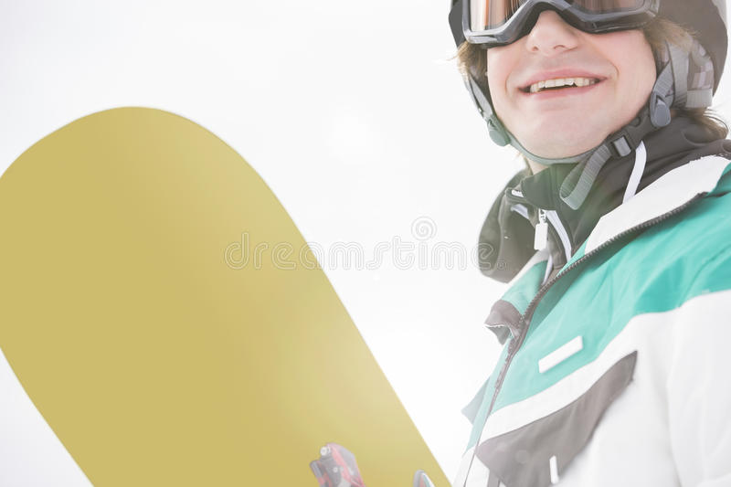 Smiling young man holding snowboard royalty free stock photos