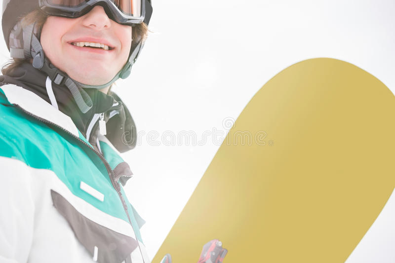 Smiling young man holding snowboard royalty free stock images