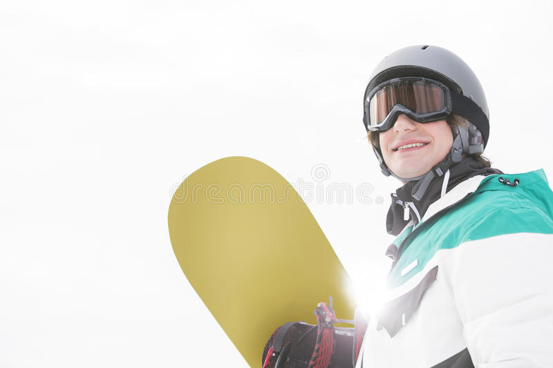 Smiling young man holding snowboard against clear sky stock photos