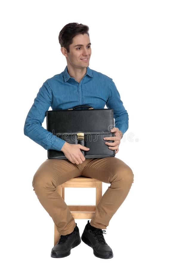 Smiling young man holding suitcase and looking to side royalty free stock images