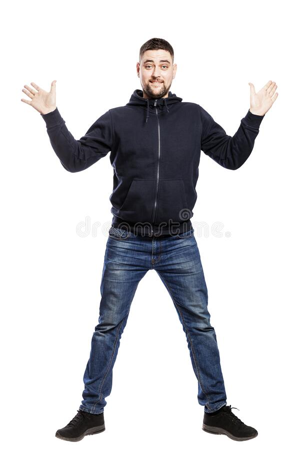 Smiling young man in jeans and a hoody is jumping. Full height. Isolated over white background. stock photo