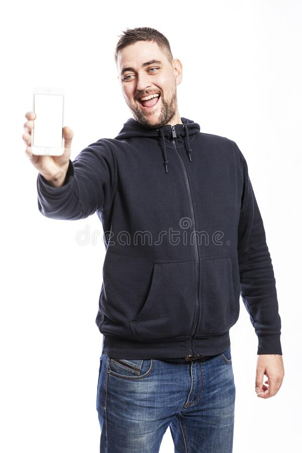 Smiling young man in jeans shows an isolated phone screen. Isolated over white background. Space for text stock photo