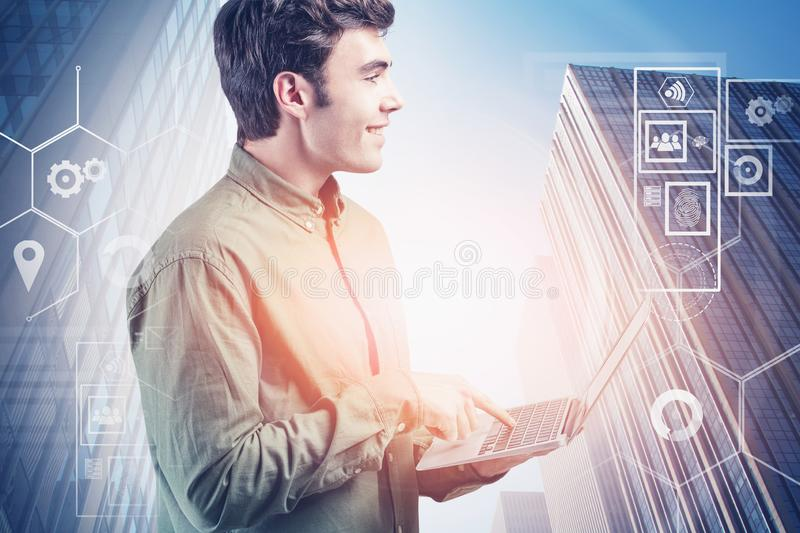 Smiling young man with laptop, digital interface. Smiling young programmer wearing green shirt using laptop standing over cityscape background with double stock photo