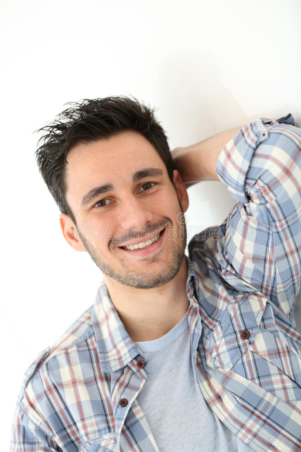 Smiling young man leaning on the wall. Smiling 30-year-old man stock photos
