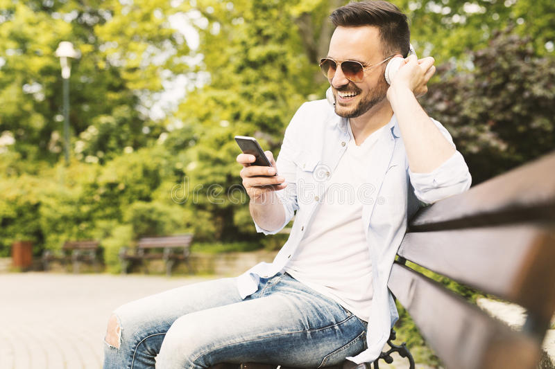 Smiling young man listening music stock images