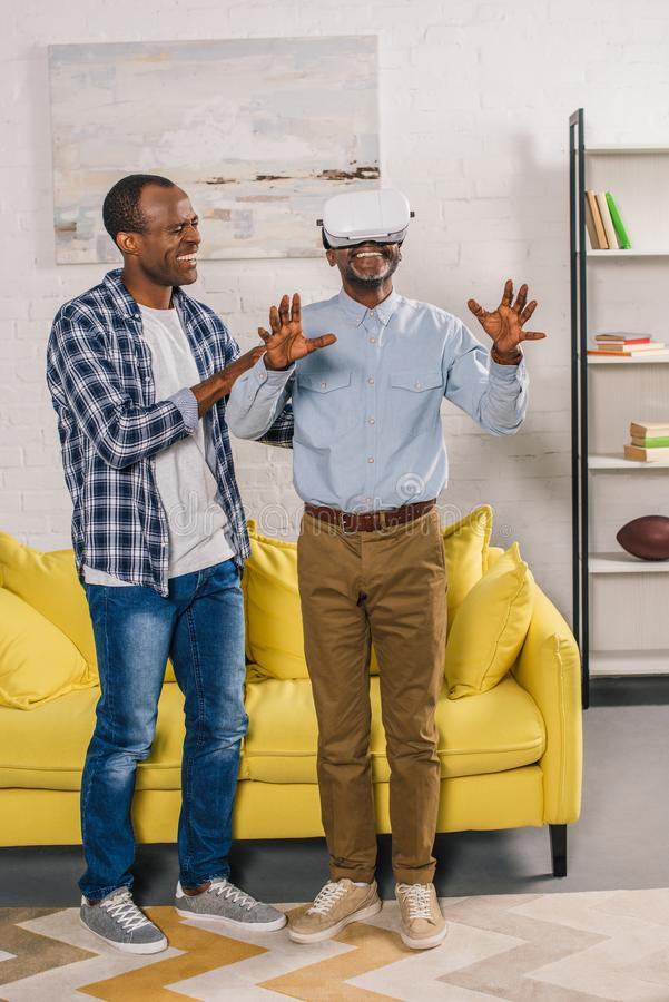 smiling young man looking at happy elderly father using virtual reality headset at home stock photography