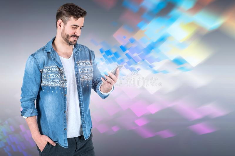 Smiling young man looks at phone digital interface. Portrait of smiling young man in jeans shirt looking at his smartphone standing with hand in pocket over dark stock photography