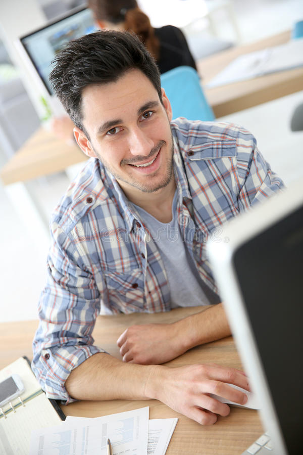 Smiling young man at office. Smiling young adult in training course royalty free stock photo