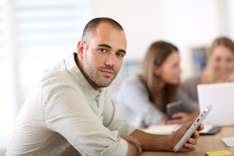 Smiling young man at office with coworkers beside stock photos
