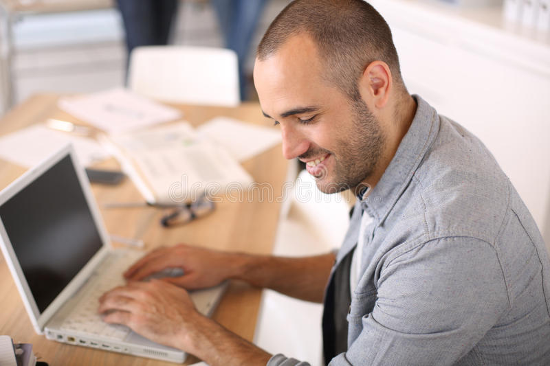 Smiling young man at office working on laptop royalty free stock photos