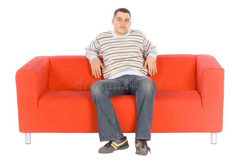 Download Smiling Young Man On Orange Couch Stock Image - Image: 1705637