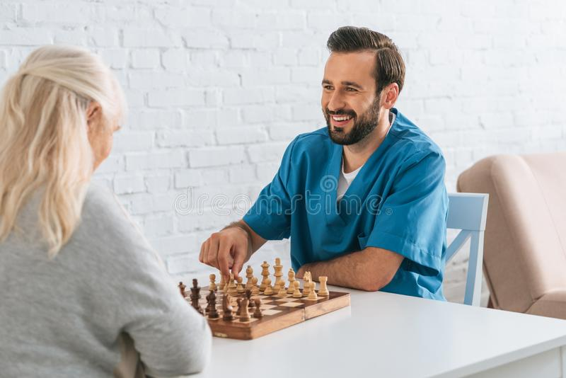 smiling young man playing chess with senior woman elderly royalty free stock images