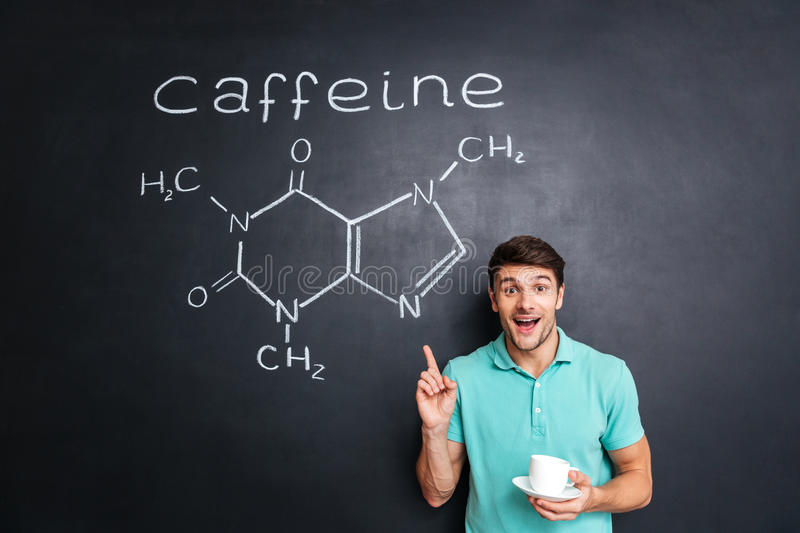 Smiling young man pointing on drawn caffeine molecule chemical structure. Smiling young man drinking coffee and pointing on drawn caffeine molecule chemical stock photography