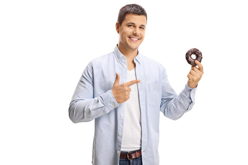 Smiling young man pointing to a donut in his hand royalty free stock photos