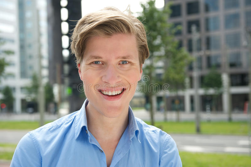 Smiling young man posing outside stock photography