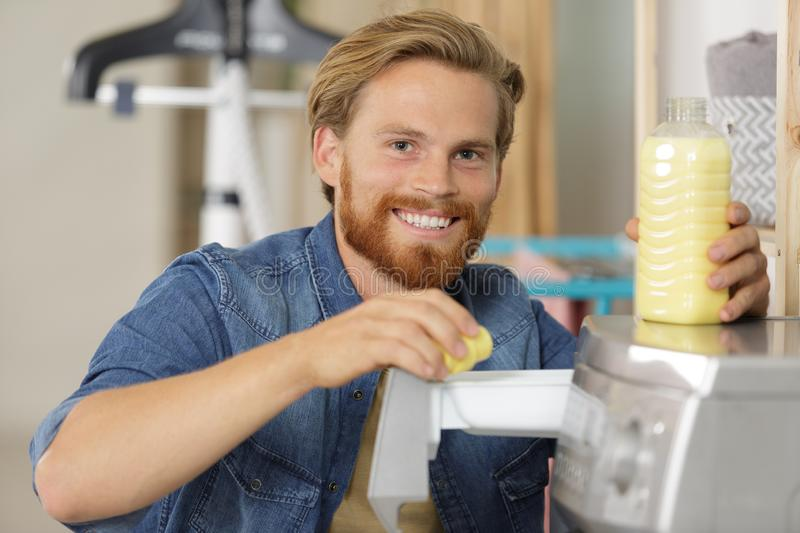 Smiling young man pouring liquid detergent in washing machine stock photo