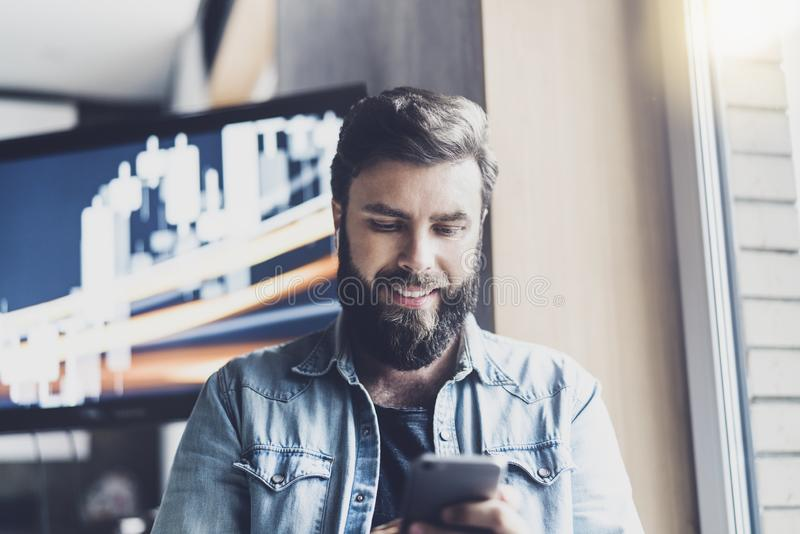 Smiling young man reading text message on his smartphone. Bearded hipster sending sms and checking email on his mobile phone stock photography