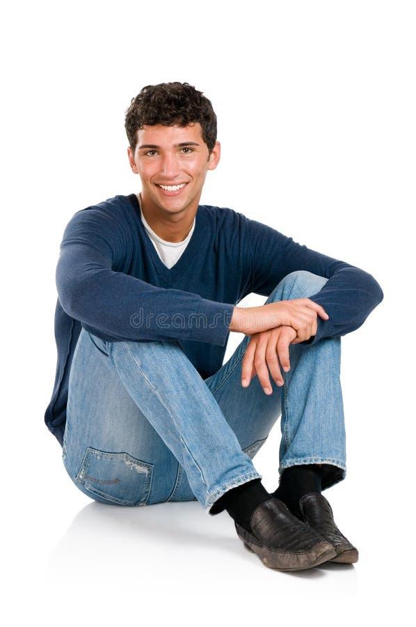 Smiling young man sitting stock photos