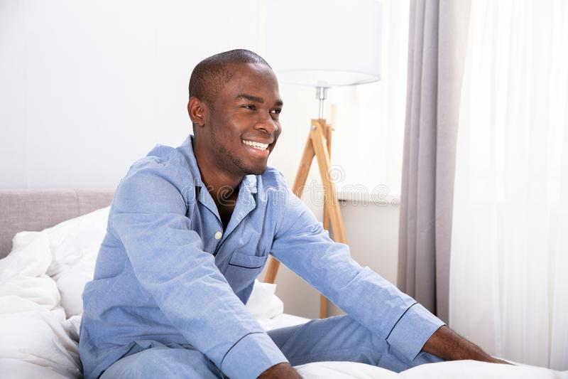 Smiling Young Man Sitting On Bed stock image